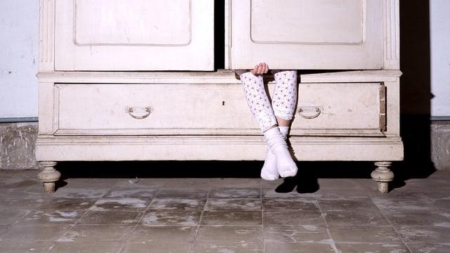 Kind sitzt im Schrank, hält die Schranktür zu – nur die Beine schauen noch raus.