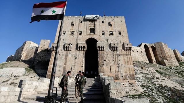 Soldaten vor einem Gebäude. An einem Fahnenmast weht die syrische Flagge.