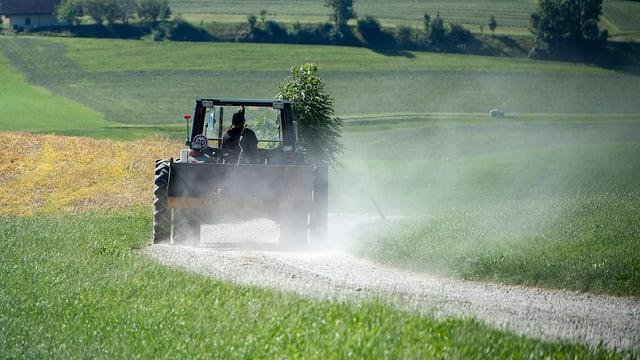Ein Bauer fährt mit seinem Traktor über einen Feldweg und wirbelt viel Staub auf.