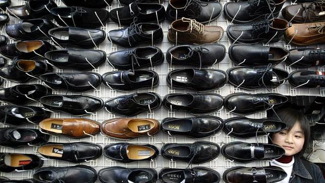 Gefälschte Schuhe in einem Gestell stehend.