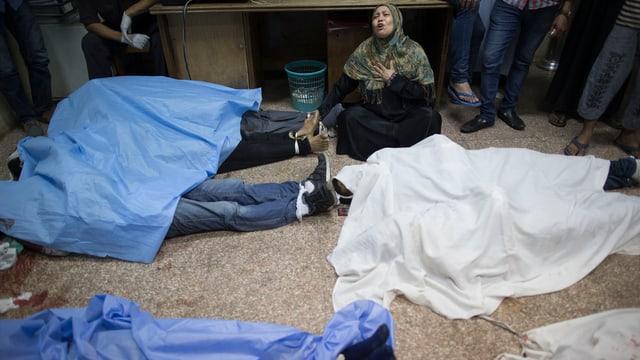 Mehrere Leichen liegen unter Tüchern, eine Frau klagt.