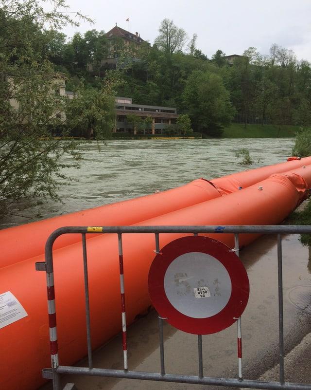 Ein Fahrverbot vor einem überschwemmten Uferweg.