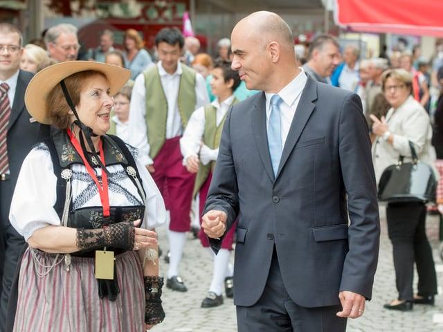 Frau in Tracht mit Mann in Zug in Strasse. Viele Menschen im Hintergrund.