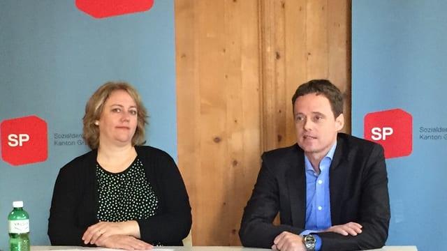 Eine Frau und ein Mann sitzen an einer Medienkonferenz vor den Journalisten.
