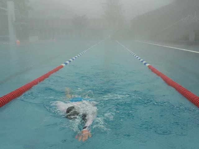 Ein Schwimmer in Neopren in einem Schwimmbecken.