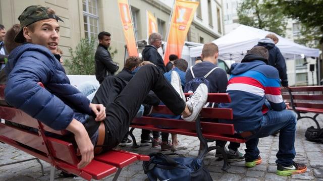 Jugendliche sitzen auf Bänken.