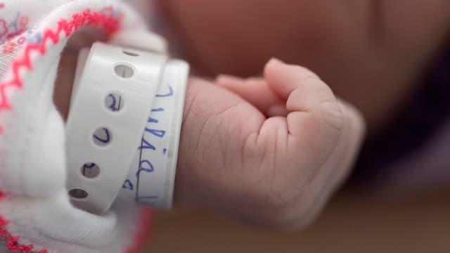 Arm mit Namensschild am Handgelenk eines Neugeborenen