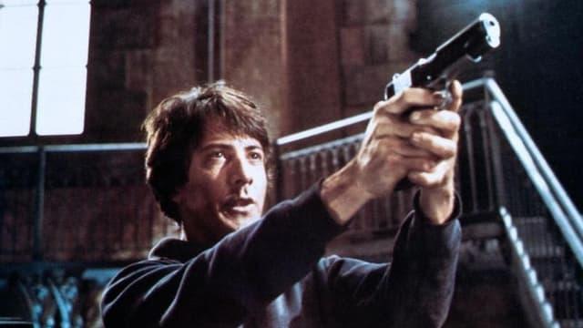 Ein Mann mit einer Waffe in den Händen.