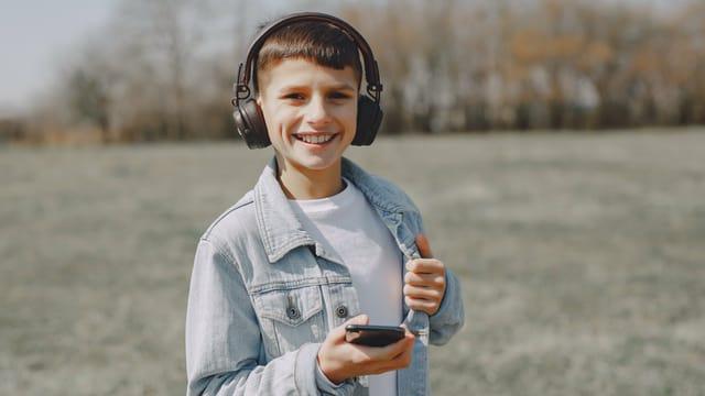 Ein Junge hört Radio über Kopfhörer