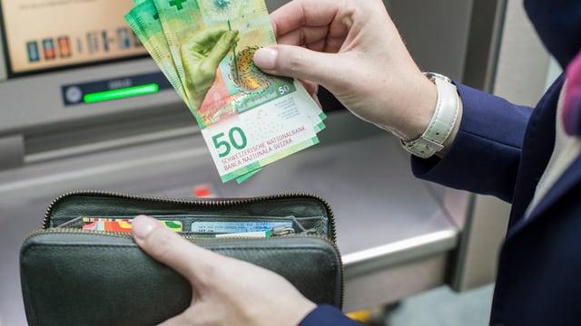 Jemand legt neue 50er-Scheine aus einem Bankomaten in eine Brieftasche,