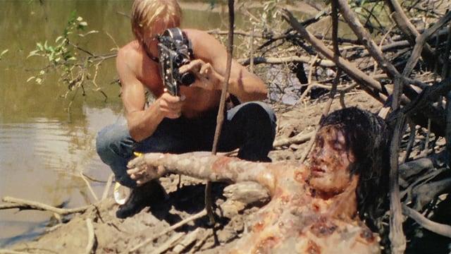 Ein Mann filmt eine blutüberströmte Leiche.