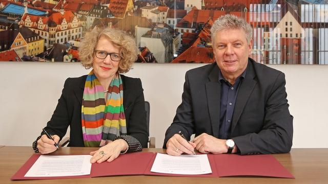 Eine Frau mit blonden Haaren und farbigem Schal und ein Mann mit grauen Haaren unterschreiben ein Papier.