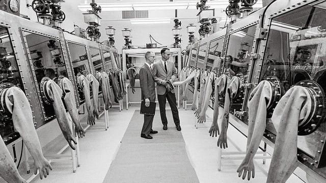 Zwei Männer stehen in einem langen Gang, der rechts und linkgs gesäumt ist mit Glasboxen, von welchen Gummihandschuhe herunterhängen, mit welchen man in die Box greifen kann.
