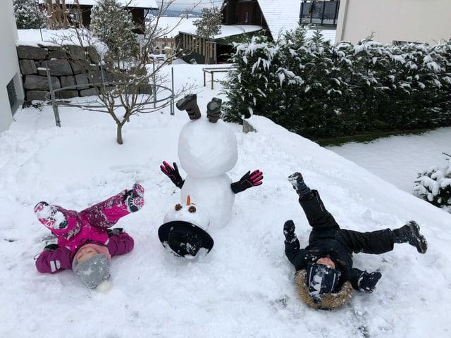 Ein Schneemann und zwei Kinder strecken die Füsse in die Luft.