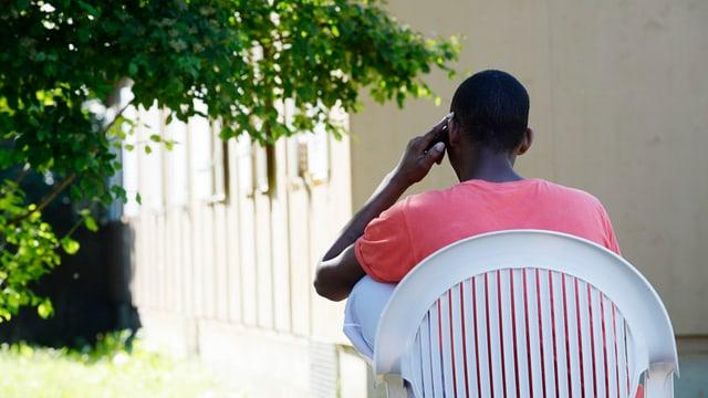 Ein Mann sitzt in einem Stuhl und telefoniert.