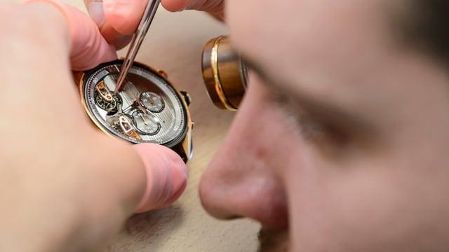 Symbolbild: Uhrmacher arbeitet an einem Uhrwerk.