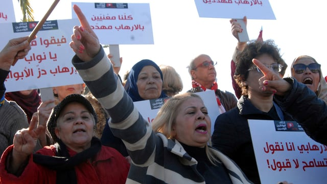 Demonstrants a Tunis che tegnan placats.