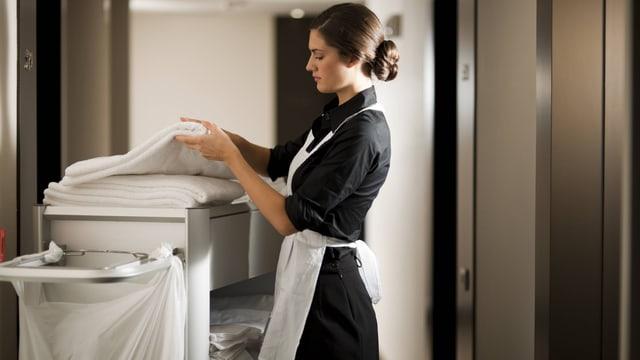Ein Totel-Zimmermädchen nimmt frische Tücher von einem Wagen.