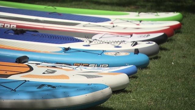 Stand-up-Paddle-Boards aufgereiht.