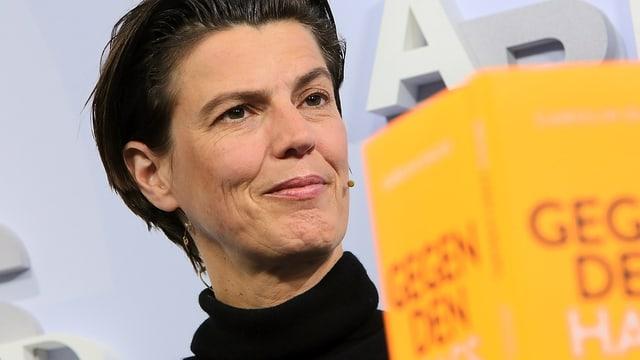 Porträt der Publizisitin Carolin Emcke vor orangem Hintergrund.
