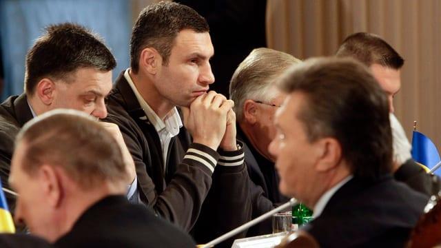 Mehrere nachdenkliche Männer an einem Tisch. In der Mitte scharf gestellt der Oppositionsführer Vitali Klitschko.