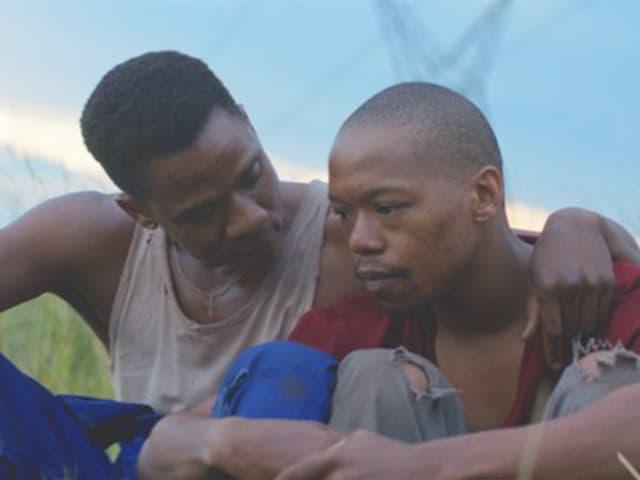 Zwei schwule Südafrikaner sitzen gemeinsam im Gras.