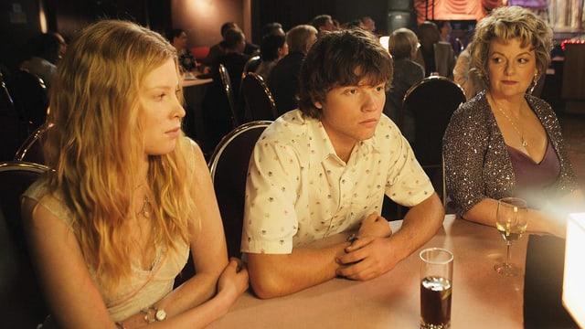 Ein junger Mann sitzt leicht genervt in der Mitte an einer Bar. Links von ihm sitzt seine Freundin, rechts von ihm seine Mutter, welche ihn etwas skeptisch betrachtet.