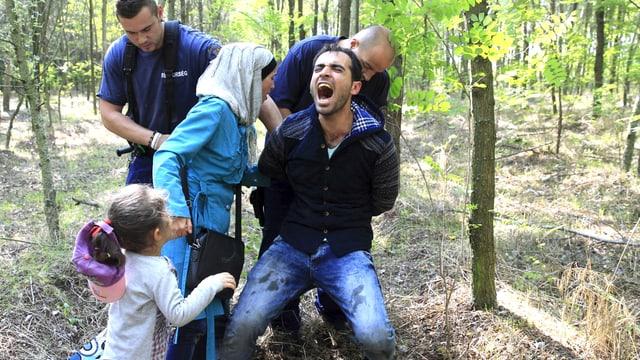 Eine Familie aus Syrien wird in einem Waldstück in Ungarn gefasst. Dem Mann werden die Hände gefesselt. Er schreit. Frau und Kind stehen daneben. (reuters)
