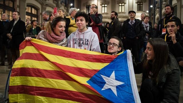 Menschen stehen hinter einer katalonischen Flagge und lachen.