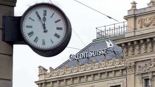 Uhr, die fünf vor zwölf zeigt, im Hintergrund Credit-Suisse-Logo auf Hausdach.