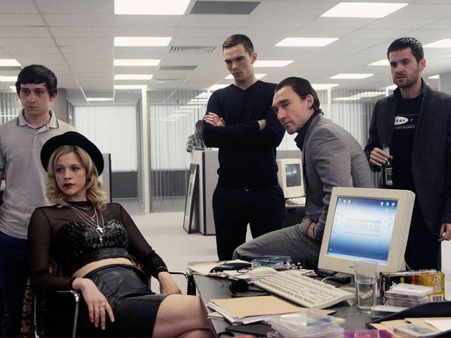 Szene aus Film. Frau sitzt lässig im Stuhl zurückgelehnt, bauchfrei und mit Hut und Männer stehen herum. Alle schauen in eine Richtung.