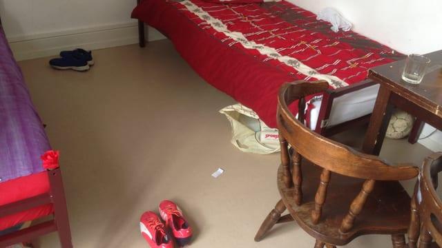 Ein Zweierzimmer mit einem kleinen Tisch, unter einem Bett liegt ein Fussball, am Boden liegen Schuhe.