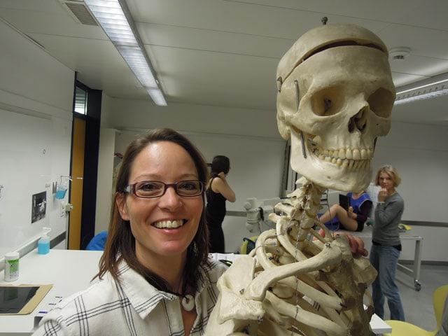 Eine lachende Frau neben einem Skelett.