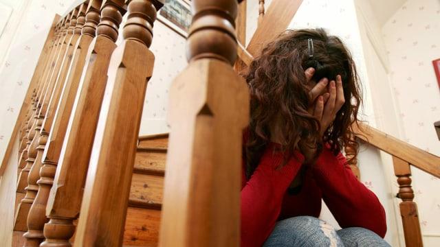 Eine Frau sitzt auf einer Treppe und weint.