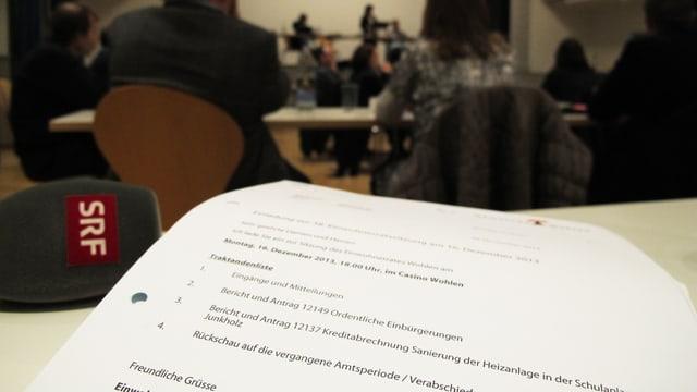 Traktandenliste der Sitzung, im Hintergrund unscharf die Parlamentarier an der Sitzung.