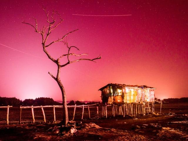 Fotografie einer Hütte in der Wüste, die rot leuchtet.