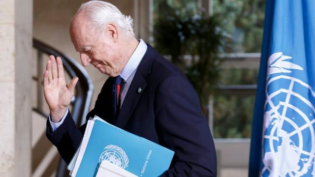 Staffan de Mistura, der UNO-Gesandte für Syrien steht neben der UNO-Flagge.