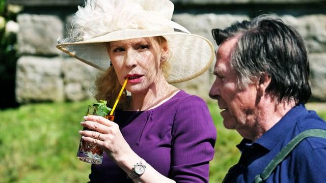 Szene draussen: Eine Frau mit grossem Hut trinkt einen Drink, ein Mann steht daneben.