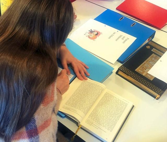 Blick über die Schulter eines jugendlichen Mädchens, das am Tisch sitzt und ein Buch liest.