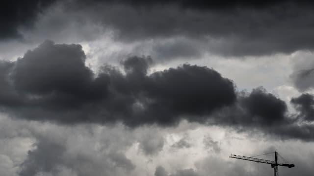 Schwarze Wolken und im Vordergrund ein Baukran