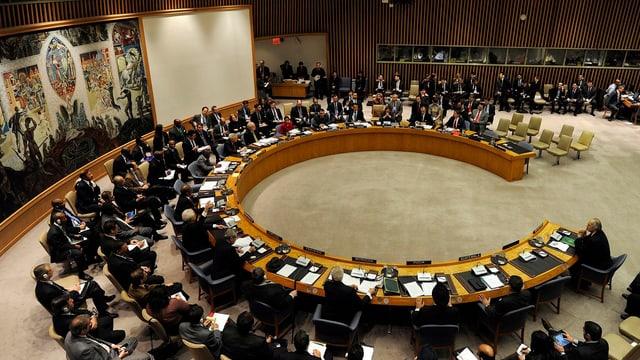 Der Weltsicherheitsrat. Ein Dreiviertelkreis. Die Mitglieder sitzen am Tisch.