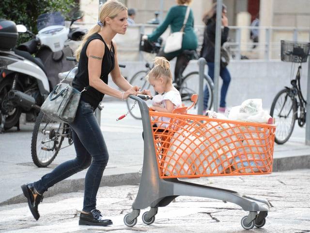 Auf der linken Seite sieht man Michelle Hunziker, die den Einkaufswagen schiebt. Im Einkaufswagen sitzt ihre Tochter Sole.