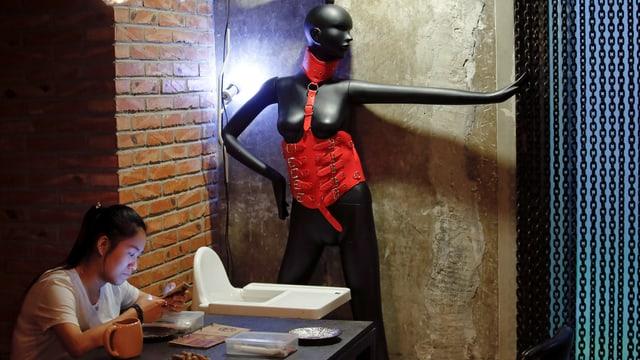 Eine Frau sitzt an einem Café-Tisch, im Hintergrund ein Mannequin mit SM-Outfit.