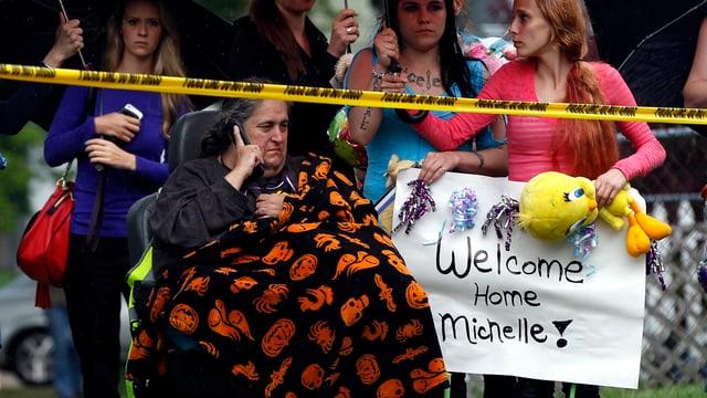 Michelles Grossmutter im Rollstuhl sowie zahlreiche junge Frauen mit einem Wilkommensschild für Michelle.