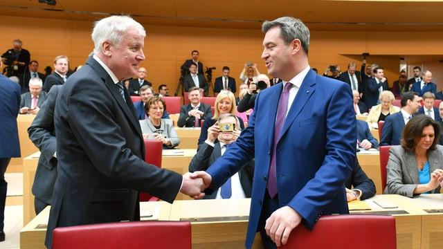 Seehofer und Söder geben sich im bayrischen Parlament die Hand.