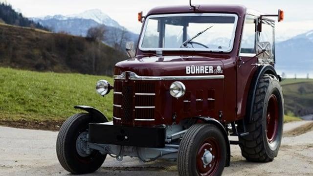 Alter weinroter Traktor der Marke Bührer steht auf einem Feldweg.