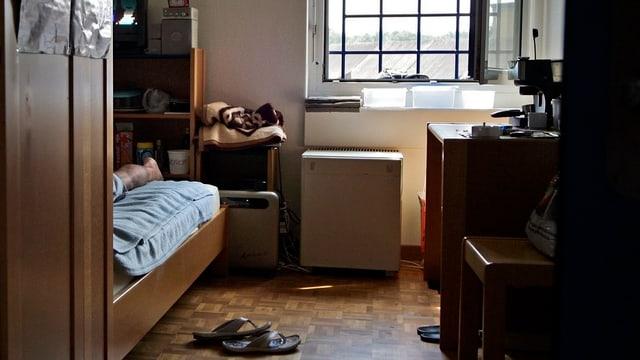 Der Blick in eine Gefängniszelle: Darin zu sehen ein Fenster mit Gittern, den Rand eines Betts mit einem Mann darauf.