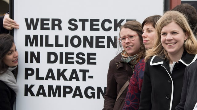 Das Initiativkomme der Transparenz-Initiative mit einem Plakat.