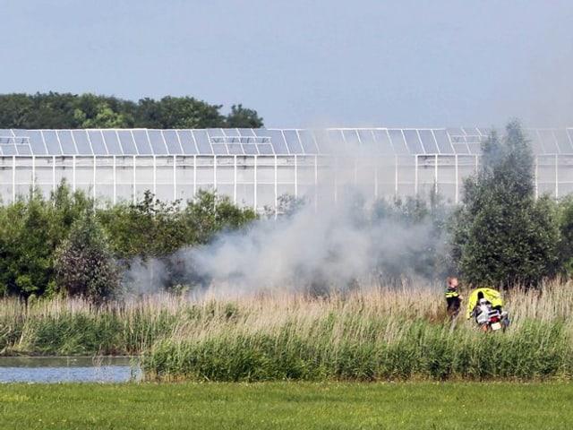 Der rauchende Absturzort in einem Teich. Im Hintergrund ein riesiges Gewächshaus.