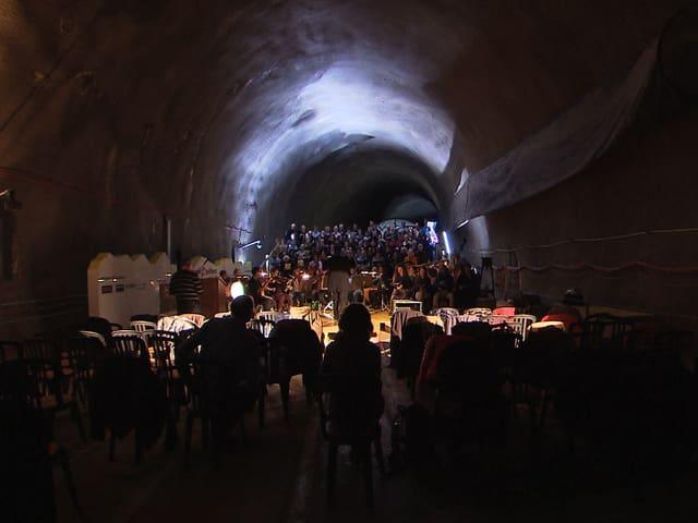 Ein Chor probt in einem spärlich beleuchteten Tunnel.